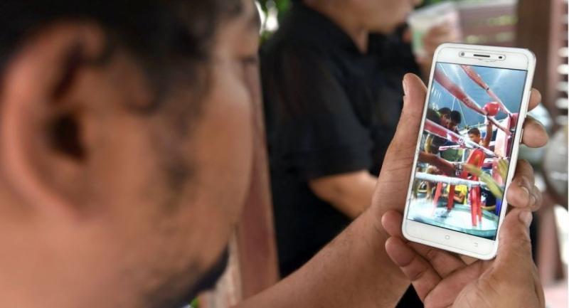 Boxing coach Somsak Deerujijaroen watches a video of thirteen-year-old Muay Thai boxer Anucha Tasako, taken during his final bout, during his funeral at a Buddhist temple in Samut Prakan province on November 14, 2018. // AFP PHOTO