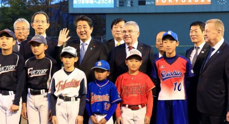 International Olympic Committee president Thomas Bach (C) and Japan's Prime minister Shinzo Abe (6th L) visit the Azuma Baseball Stadium field in Fukushima on November 24, 2018. (Photo by JIJI PRESS / JIJI PRESS / AFP)