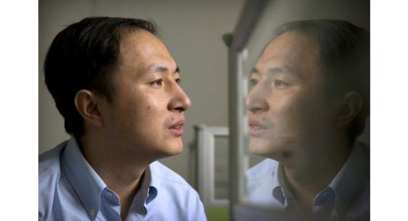 He Jiankui is reflected in a glass panel as he works at a computer at a laboratory in Shenzhen in China. [Photo/Agencies]