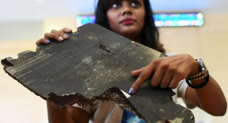 Grace Subathirai Nathan (R), daughter of Malaysian Airlines flight MH370 passenger Anne Daisy, shows a piece of debris believed to be from flight MH370 during a press conference in Putrajaya on November 30.//AFP