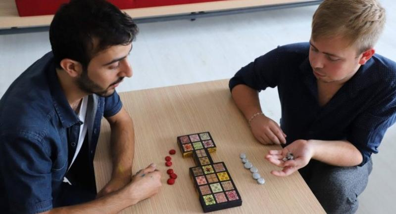 Iraqi artist Hoshmand Mofaq and British archaeologist Ashley Barlow, right, play an ancient board game, known as the Royal Game of Ur, in the northern Iraqi city of Raniey. /AFP