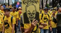 In this file photo taken on November 19, 2016, a protester holds a placard with a caricature depicting Malaysian Prime Minister Najib Razak during a mass rally calling for Razak's resignation, in Kuala Lumpur. /AFP