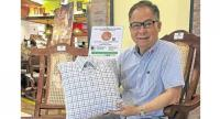 Tito Alcala with a Love Pillow, seated on his donated Silya rocking chair.
