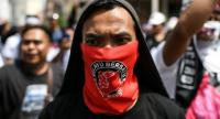 A protester covers his face with a banner reading