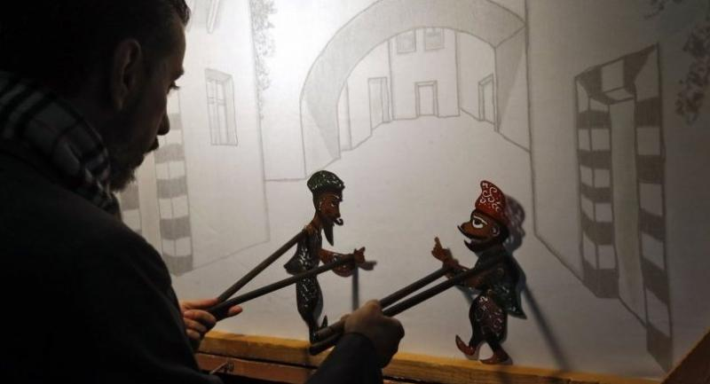 Syria's last shadow puppeteer Shadi al-Hallaq is seen moving his puppets Karakoz, right, and Eiwaz, left, from inside his booth during a presentation in Damascus. /AFP