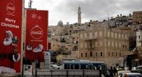 Advertising posters, celebrating Christmas, are seen displayed on buildings in front of the main houses of the Old City of the occupied West Bank biblical city of Bethlehem, on December 12.//AFP