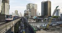 A suburban train passes a building site in central Bangkok. The construction boom continues amid signs of a slowdown next year.--AFP