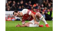 Arsenal's Henrikh Mkhitaryan takes a knock needing attention on the field during the English League Cup match between Arsenal and Tottenham Hotspur.