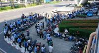 Taxi drivers queue to apply to hire-purchase loans provided by the Small and Medium Enterprise Development Bank of Thailand ahead of the formal of approval of the assistance scheme yesterday.
