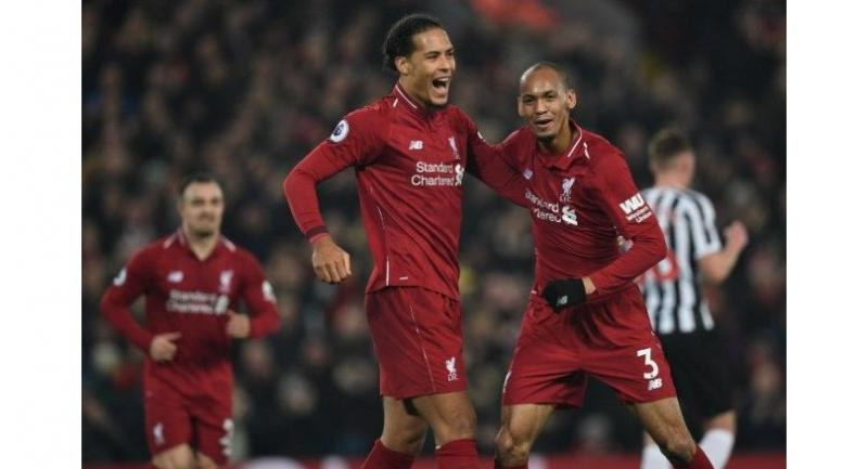 Brazilian midfielder Fabinho (R) celebrates with Dutch defender Virgil van Dijk (C) after scoring their fourth goal during the EPL football match between Liverpool and Newcastle United.