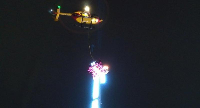 A helicopter hovers over a giant funfair ride after eight people got stuck high in the air in the Brittany city of Rennes late on December 31, 2018.  // AFP PHOTO