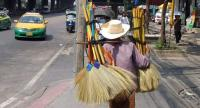 An elderly woman carries broomsticks as she hopes to sell them for a living on a Bangkok street. She is among millions of Thais who get old before accumulating enough savings for a comfortable retirement life.