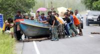 Fishermen yesterday move their boats up on to the road at Laem Talumphuk in Pak Phanang district, Nakhon Si Thammarat province, as they brace for tropical storm Pabuk.