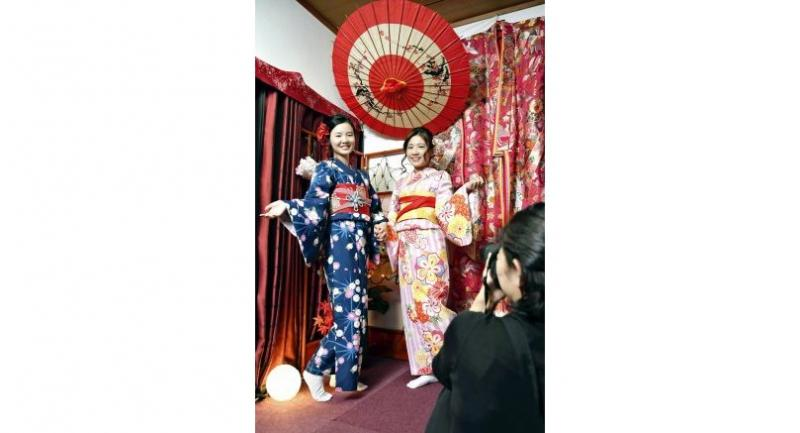 After changing into kimonos at Hanaka, visitors from Hong Kong have their picture taken.
