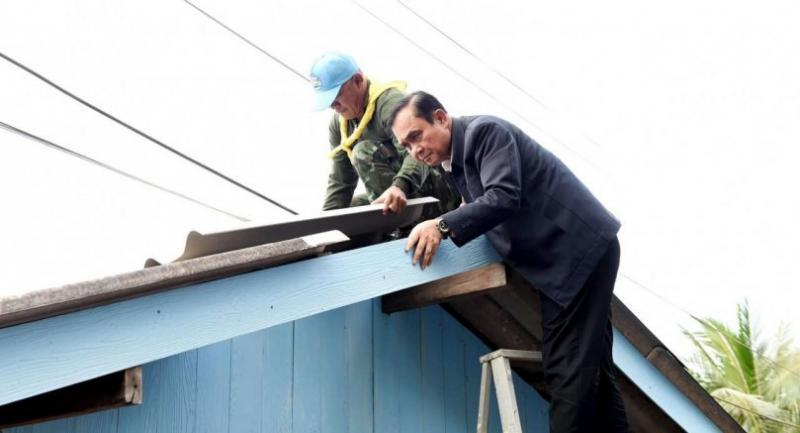 Prime Minister General Prayut Chan-o-cha yesterday helps fix the roof of a damaged house in Nakhon Si Thammarat province, which was hard-hit by tropical storm Pabuk.