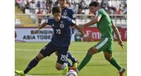 Japan's defender Hiroki Sakai (L) fights for the ball against Turkmenistan's forward Vakhit Orazsakhedov.