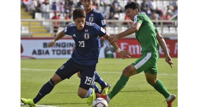 Japan's defender Hiroki Sakai (L) fights for the ball against Turkmenistan's forward Vakhit Orazsakhedov.