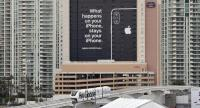 A monorail train passes by a billboard advertising Apple's iPhone security during CES 2019. /AFP