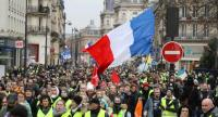 Demonstartors wave a giant French national flag as they march on rue de Rivoli, near place de l'Hotel ville, in Paris, on January 12, 2019 during anti-government demonstration called by the Yellow Vest