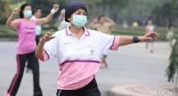 Many people wear masks as they attend aerobic workouts at Lumpini Park in central Bangkok yesterday. The PM2.5 level has been dangerously high, covering the capital with thick smog.  PhotoAnant Chantarasoot