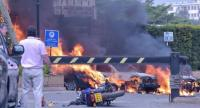 Two men stand next to burning cars at the scene of an explosion at a hotel complex in Nairobi on January 15.//AFP