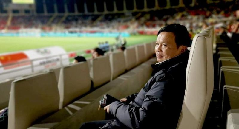 I spy: Sirisak Yodyadthai watches from the stands as Thailand's next opponents, China or South Korea, meet in their group finale onWednesday. China lost the game so Thailand will play them in the round of 16.