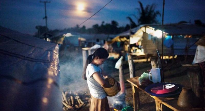 Six months after her home was washed away in the collapse of the dam, a woman cooks dinner behind her tent in Pindong camp. // Visarut Sankham