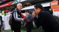 Sirisak Yodyadthai performs a Thai wai to China's coach Marcello Lippi after the game.