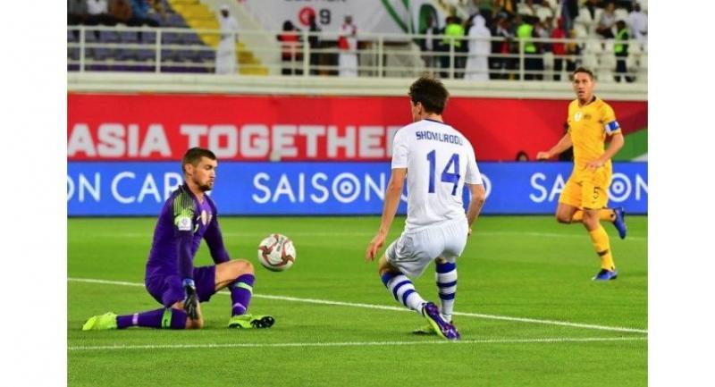 Australia's goalkeeper Mathew Ryan (L) controls the ball as he is closed Uzbekistan's forward Eldor Shomurodov.