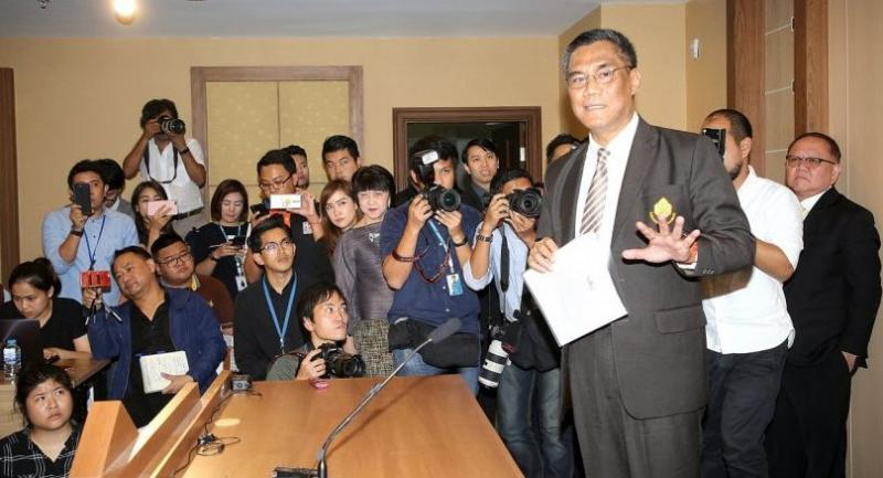 Election Commissioner Ittiporn Boonpracong is surrounded by reporters yesterday after announcing March 24 as the date for the general election.