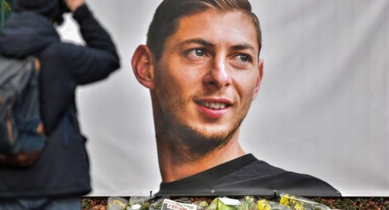 A man takes a picture of flowers displayed next to a portrait of Emiliano Sala before the entrance of the FC Nantes football club training center La Joneliere on January 23.//AFP