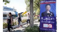 Pedestrians walk past an election campaign poster of MP candidate for the Phue Thai party, in Bangkok yesterday. // EPA-EFE PHOTO
