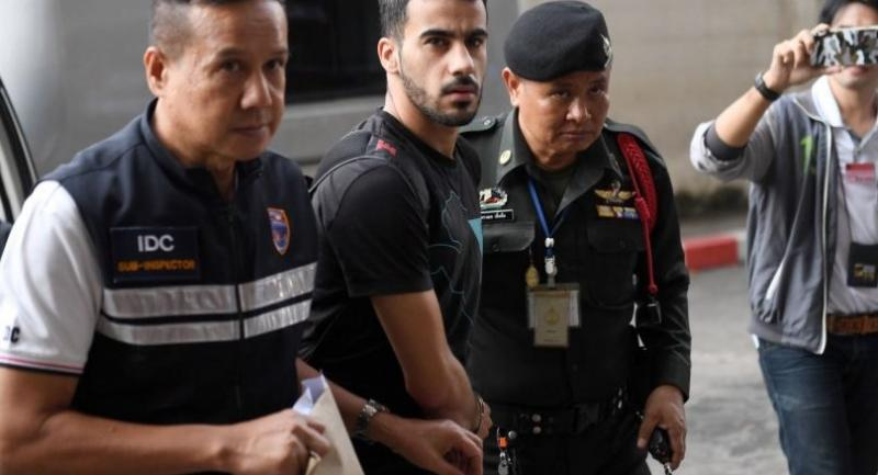 Hakeem Alaraibi (C), a former Bahrain national team footballer with refugee status in Australia, is escorted by immigration police to a court in Bangkok on December 11.//AFP
