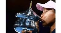Japan's Naomi Osaka poses with the championship trophy during the presentation ceremony after her victory against Czech Republic's Petra Kvitova.