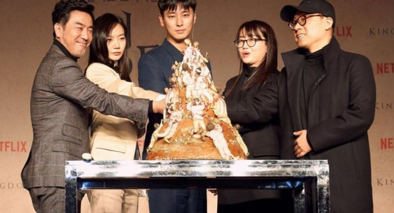 """From left Ryu Suengyong, Bae Doona, Ju Jihoon, writer Kim Eunhee and director Kim Seunghun cut a cake made to resemble the mountain of zombies from """"Kingdom"""" during the press conference in Seoul. /Netflix photo"""