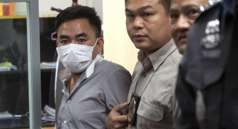 (FILES) This file photo taken on January 20, 2018 shows Boonchai Bach (L), 40, a Vietnamese national with Thai citizenship and alleged kingpin in Asia's illegal trade in endangered species, is being handled by Thai police in Bangkok after his arrest.