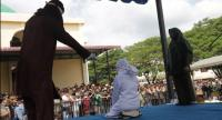 An Acehnese woman (C) is caned as punishment for having a sexual relationship outside of marriage in Banda Aceh, Aceh, Indonesiaon Thursday. // EPA-EFE PHOTO