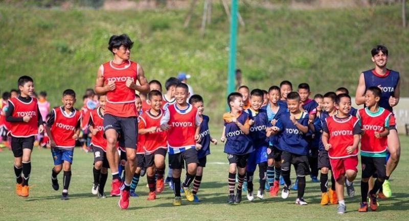 Nagoya's former captain Yuichi Maruyama and young Thai trainees.