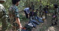 This file photo shows forest rangers from Thailand together with Cambodian and Laos rangers holding two armed