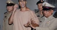 Bahraini soccer player with Australian refugee status Hakeem Al-Araibi (C) reacts to journalists as he is escorted by Thai prison officers prior an extradition hearing at the Criminal Court in Bangkok, Thailand, on February 4.//EPA-EFE