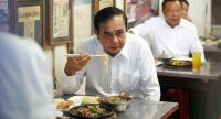 Prime Minister Prayut Chan-o-cha eats street food during his lunch at Nang Loeng market in Bangkok yesterday. // EPA-EFE PHOTO