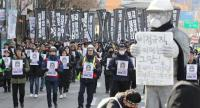 People march to honour a worker crushed to death at a coal plant, in Seoul on February 9, 2019. - Some 2,500 South Koreans marched to honour Kim Yong-kyun, 24, who died last month after being sucked into a coal conveyor belt./AFP