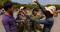A Cambodian man (R) raises a snake fish up during the annual fish-catching ceremony at Choam Krovean commune in Tboung Khmum province on February 10.//AFP