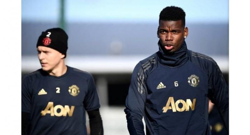 Manchester United's French midfielder Paul Pogba (R) arrives for a training session at the Carrington Training complex in Manchester.