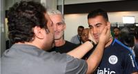 A supporter receives footballer Hakeem al-Araibi (R) upon his arrival at the airport in Melbourne with former Australian football captain Craig Foster (C) yesterday. // AFP PHOTO
