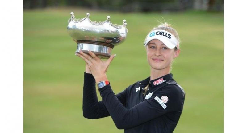Nelly Korda of the US poses with the winner's trophy. / AFP