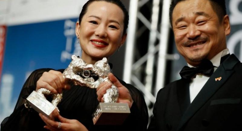 """Chinese actors Wang Jingchun and Yong Mei pose with their Silver Bears for Best Actors in the film """"Di Jiu Tian Chang?"""" (""""So Long, My Son"""") at the 69th Berlinale film festival./AFP Photo"""