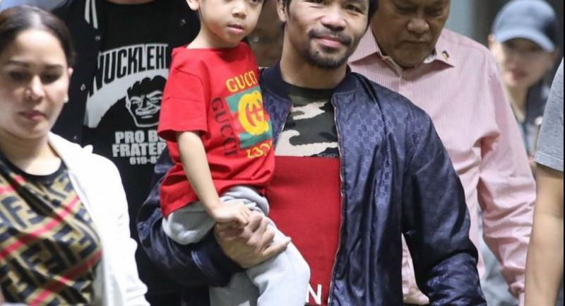 A handout photo made available by PNA shows Filipino boxing icon Manny Pacquiao carrying his son as he arrives at the Manila's international airport, Philippines, 24 January, days after defeating US boxer Adrien Broner in Las Vegas, USA.//EPA-EFE