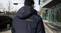 This picture taken on February 18 shows 12 digits - 615104427919 - sewn onto the back of a jacket of one of South Korea's presidential house staff members, on the street outside the presidential Blue House in Seoul.//AFP