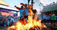 Young pilgrims show their spirit in the sacred fire walking ceremony./Photo by Khob Jai Thailand page